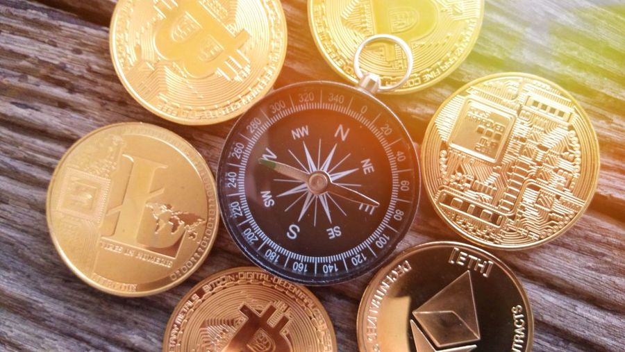 Directly above shot of navigational compass and coins on wooden table