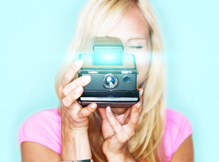 Woman photographing from polaroid camera against colored background