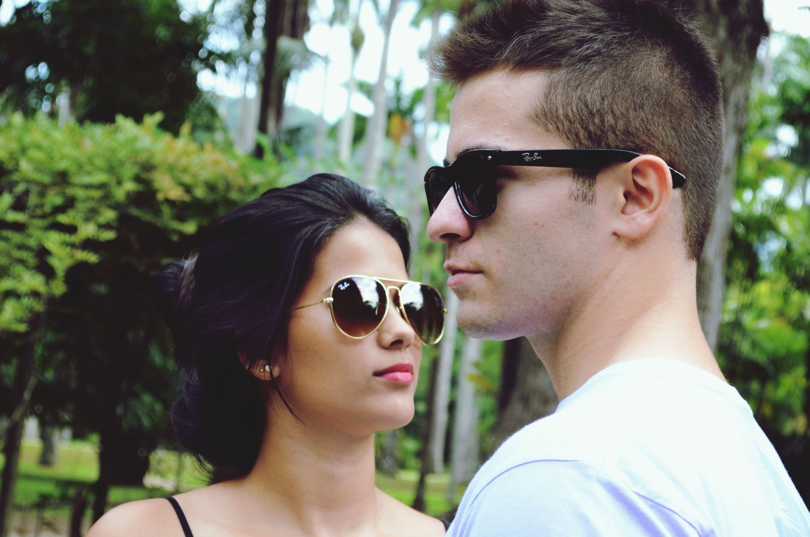 young adult, lifestyles, person, focus on foreground, leisure activity, headshot, young women, sunglasses, looking at camera, portrait, head and shoulders, close-up, smiling, front view, holding, tree