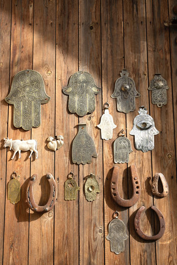 lucky charms hung on a door in a garden Wood - Material No People Indoors  Hanging Wall - Building Feature Variation Choice Close-up Brown Full Frame Metal Still Life Wood Day Large Group Of Objects Door Design Backgrounds Entrance In A Row Marrakech Garden Lucky Charms