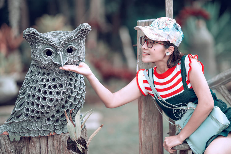 Smiling woman touching owl statue