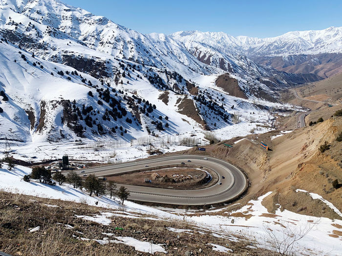 Scenic view of snowcapped mountains against sky with highway road