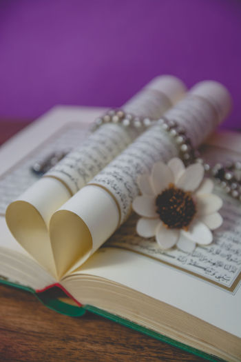 Close-up of koran with prayer beads and flower on table