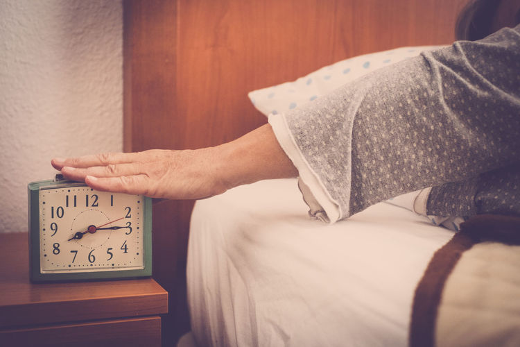 Cropped hand turning off alarm clock in bedroom at home