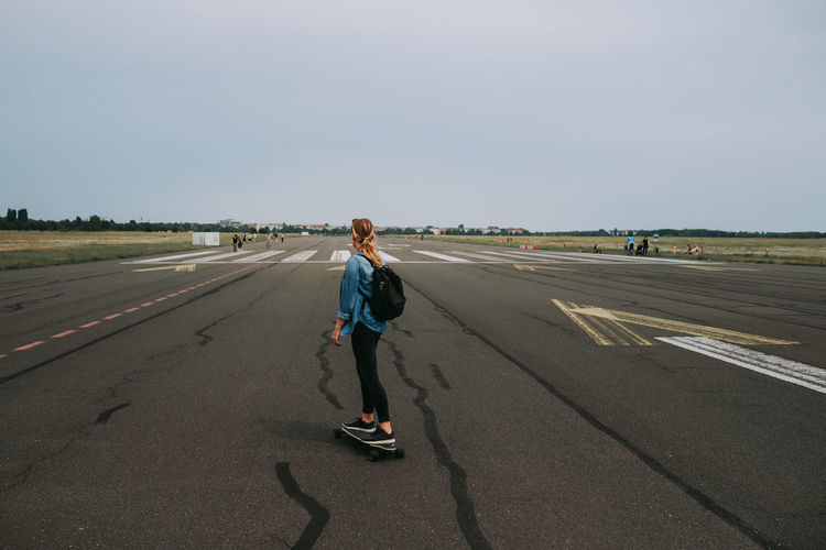 Woman with umbrella on airport runway against sky