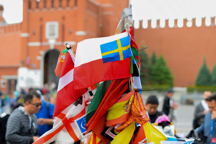 Close-up of flags and people in front of building