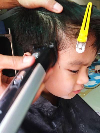 Cropped hand cutting boy hair at salon