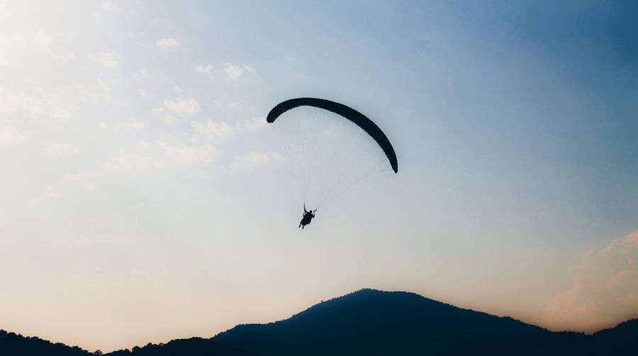 Silhouette of a paraglider Flying Mid-air Silhouette Extreme Sports Sky Motion Outdoors Paragliding Nature Day Parachute Stunt Person EyEmNewHere