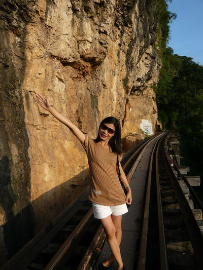 Portrait of smiling mature woman with arm raised standing on railway bridge
