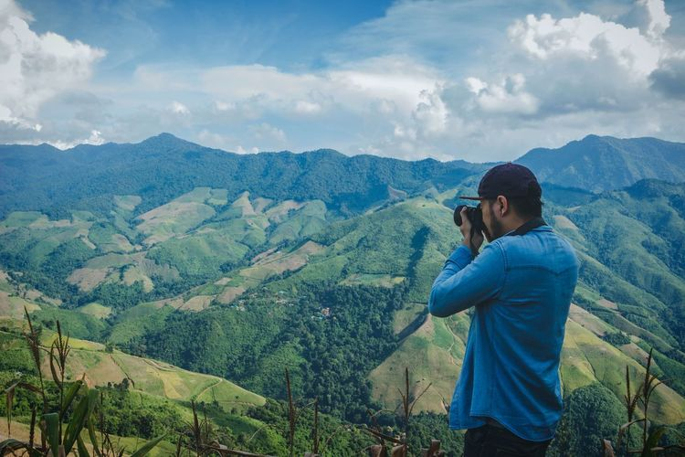 Man photographing mountains against cloudy sky