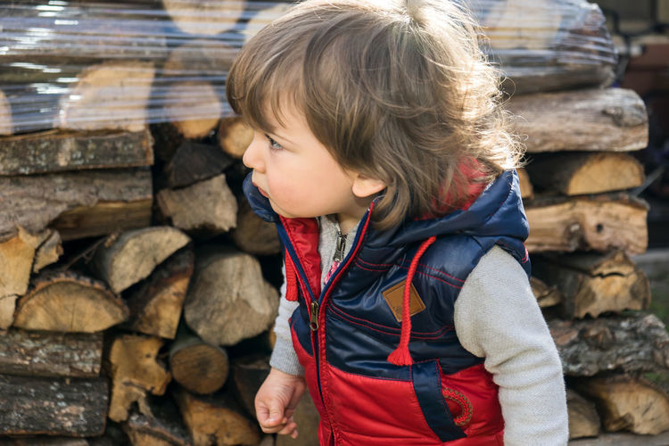 Pile Of Wood Baby Boy Boy Child Childhood Clothing Day Firewood Hair Hairstyle Leisure Activity Lifestyles Log Nature One Person Outdoors Real People Stack Women Wood Wood - Material