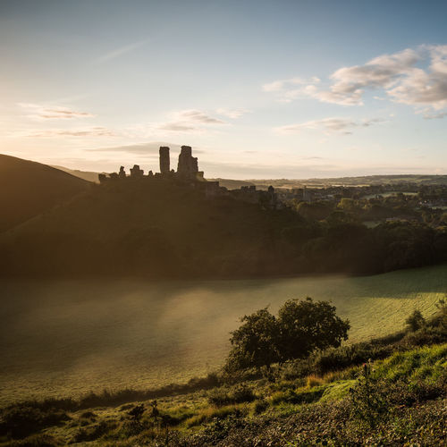 Corfe Castle at sunrise in Dorset Dorset Square Tourist Attraction  Travel Architecture Beauty In Nature Blue Sky Building Building Exterior Built Structure Cloud - Sky Corfe Castle Landscape Nature No People Outdoors Scenics - Nature Sky Sunlight Sunrise Tourism Tranquil Scene Tranquility Travel Destinations Tree
