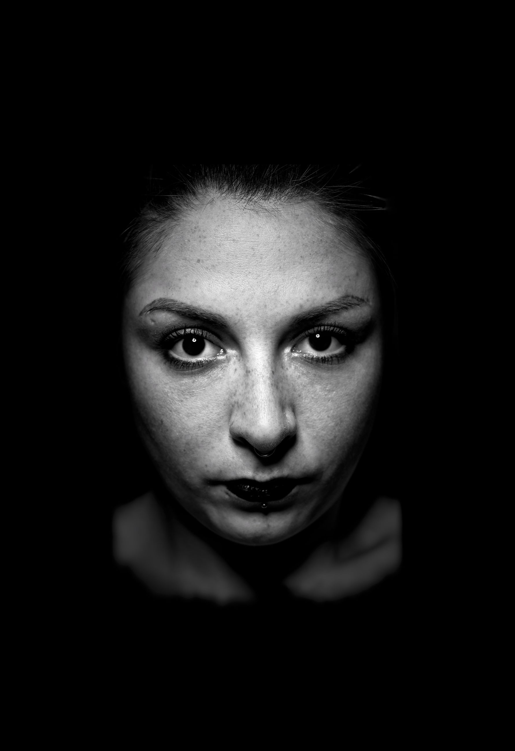 portrait, looking at camera, headshot, one person, front view, indoors, close-up, studio shot, black background, young adult, mid adult, young women, mid adult women, women, emotion, adult, body part, human body part, human face, aggression, depression - sadness
