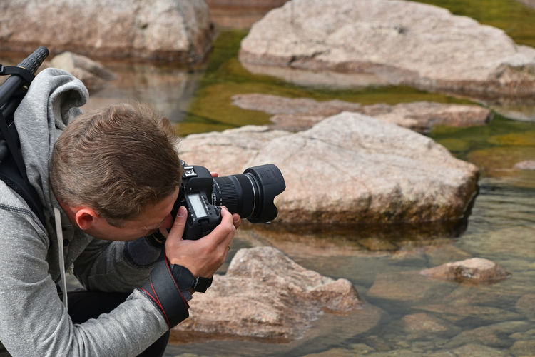 Photographer against rocks in lake