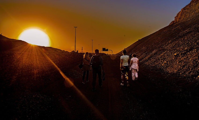 Rear view of people walking on road against sky during sunset