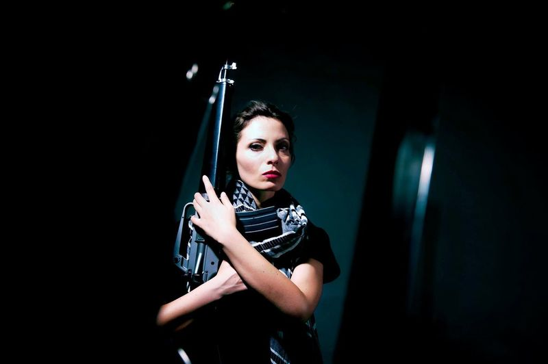 Portrait Of Woman Holding Rifle While Standing Indoors