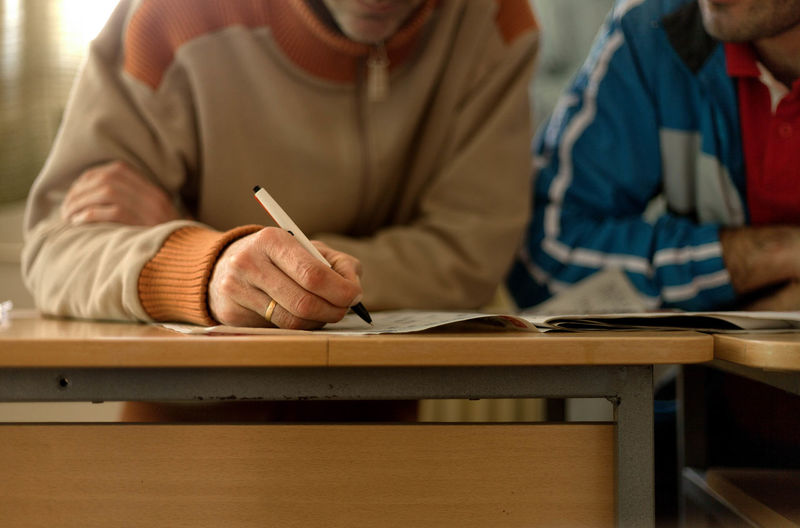 Midsection Of Man Writing On Paper While Sitting By Friend