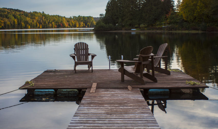 Empty deck chairs by lake against sky