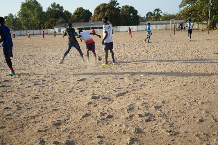 Group of people playing soccer on sand