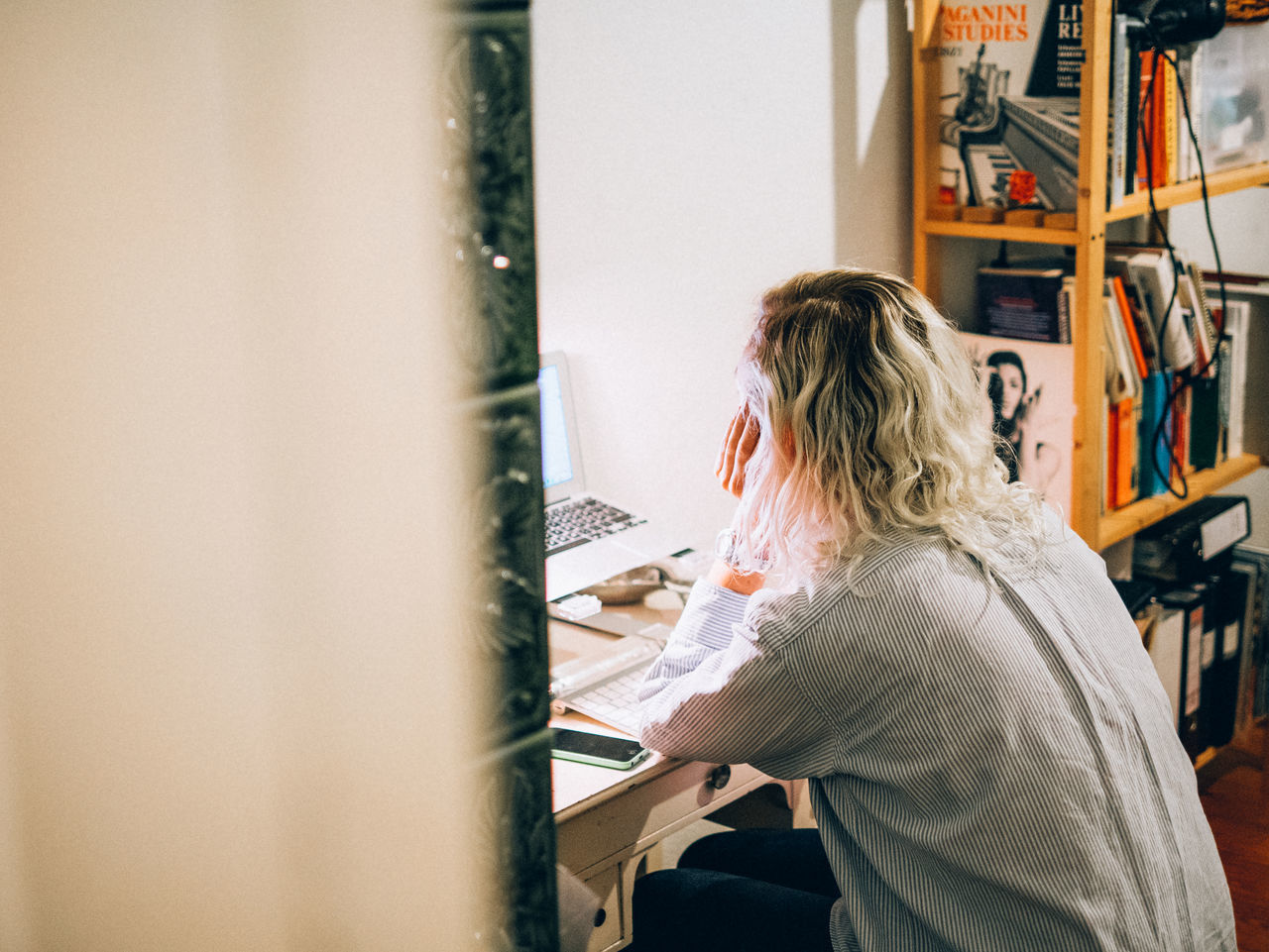 Side view of woman sitting and studying by laptop in living room