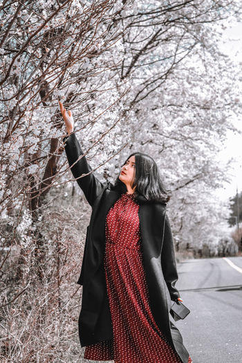 Full length of woman standing on snow covered tree