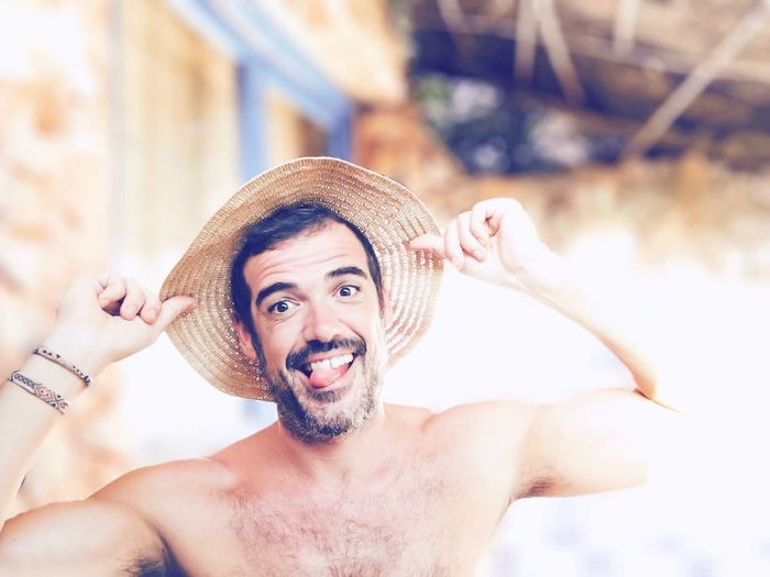 Portrait of shirtless man in hat sticking out tongue outdoors