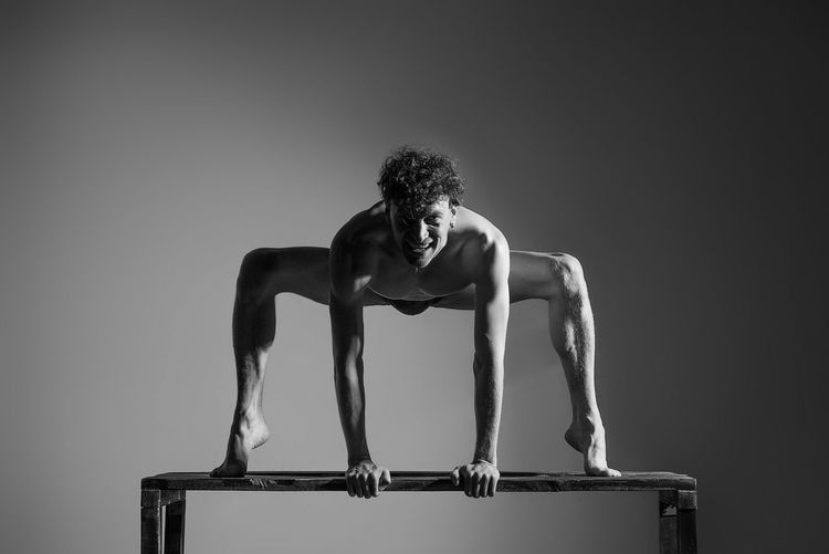 Portrait of shirtless man exercising on bench against wall
