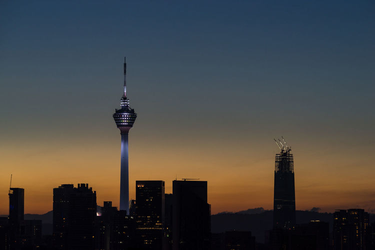 Communications tower in city against sky during sunset