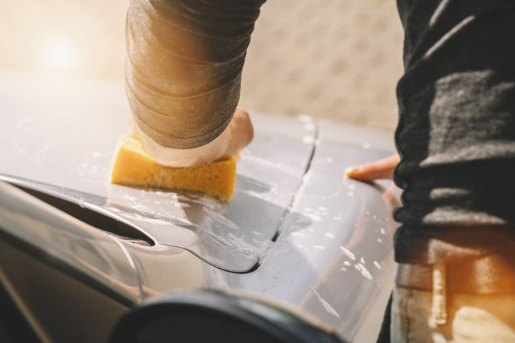 Close-Up Of Man Cleaning Car With Sponge