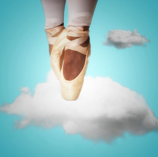 Digital composite image of ballet dancer dancing on cloud against blue background