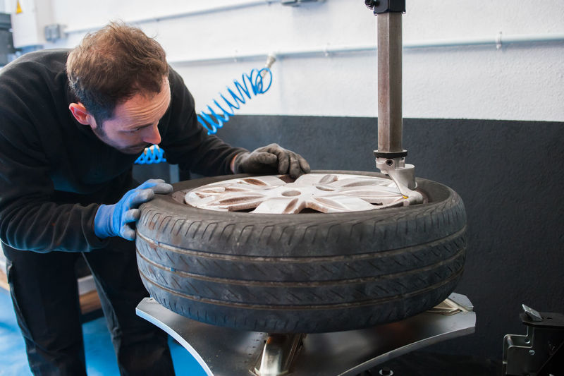 Male Mechanic Holding Tire In Auto Repair Shop