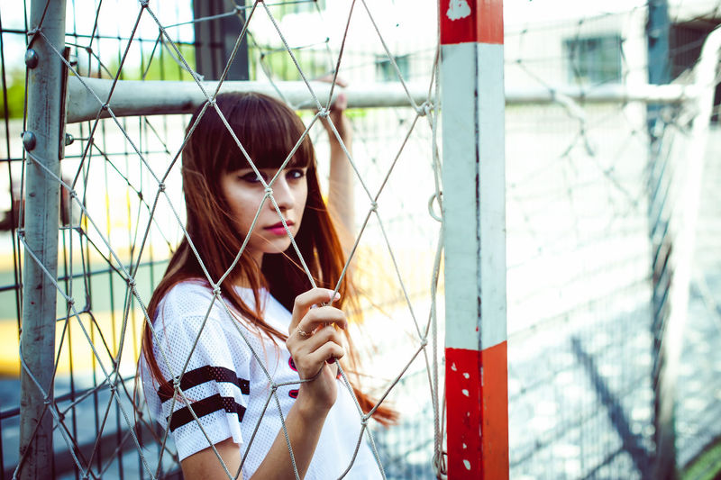 Portrait of young woman standing in goal post