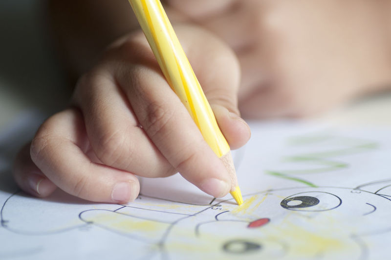 Cropped hand of child coloring drawing