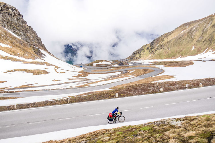 Scenic view of person riding bike on snow covered landscape