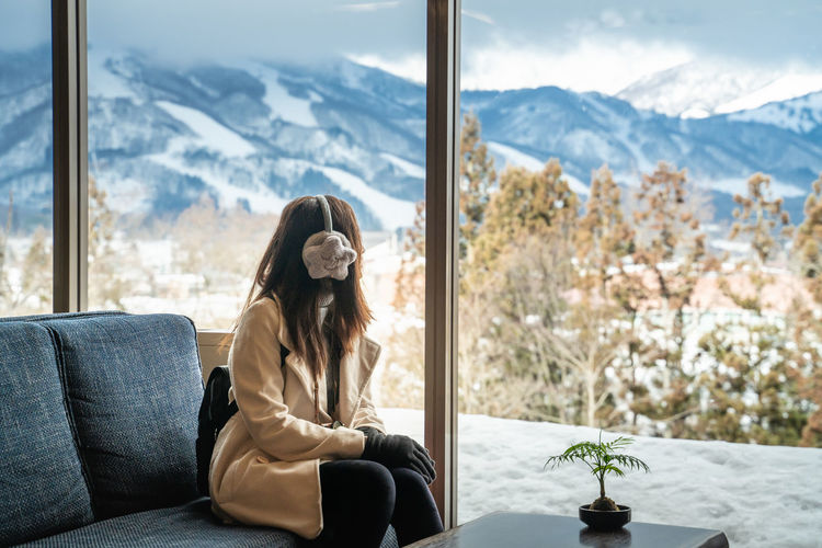 Woman looking at mountains through window while sitting on sofa