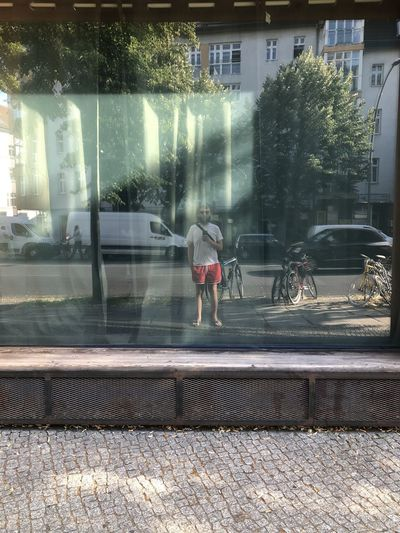 People walking on street seen through glass window