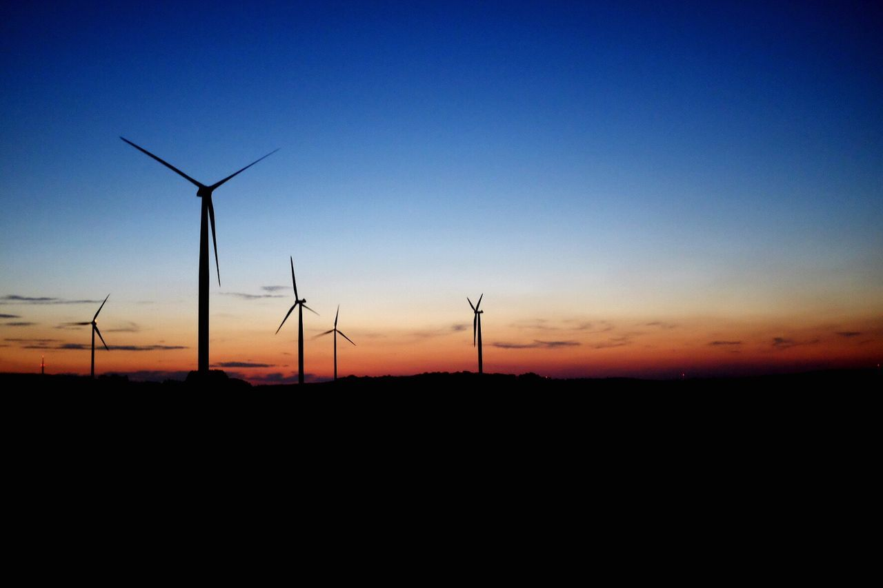 Silhouette Of Wind Turbines In Field At Sunset