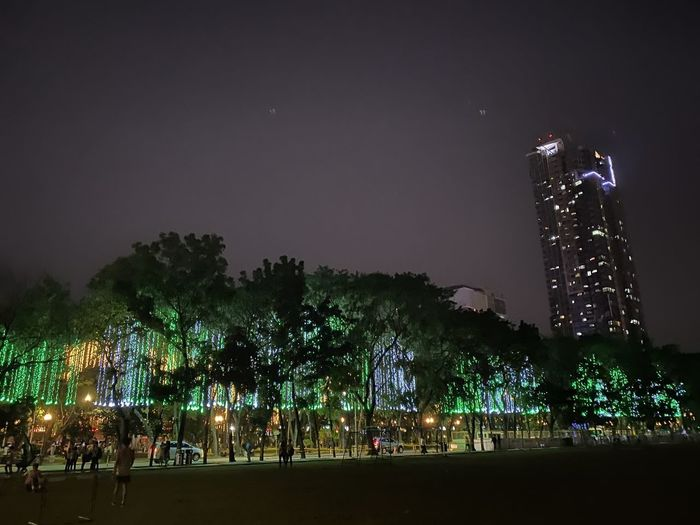 Low angle view of illuminated trees against sky at night
