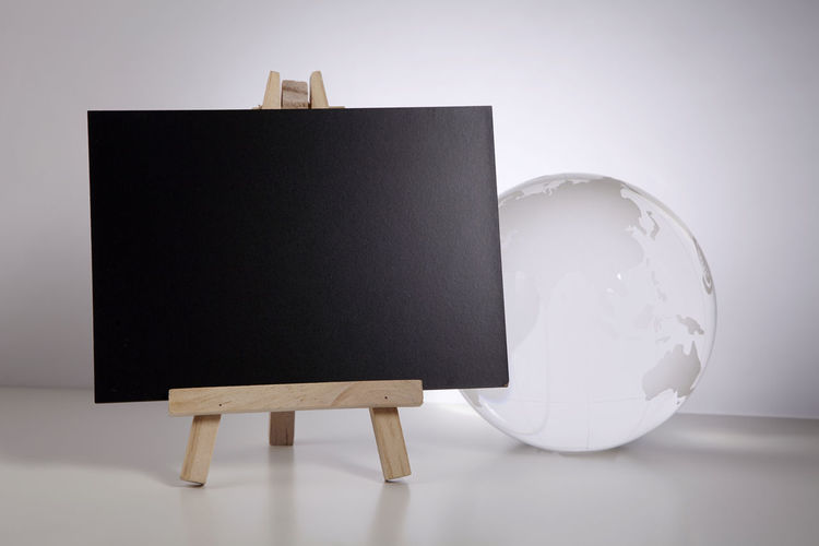 Close-up of blank blackboard and globe against white background