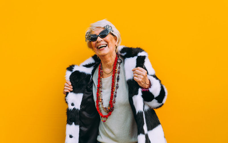 Smiling senior woman gesturing against colored background