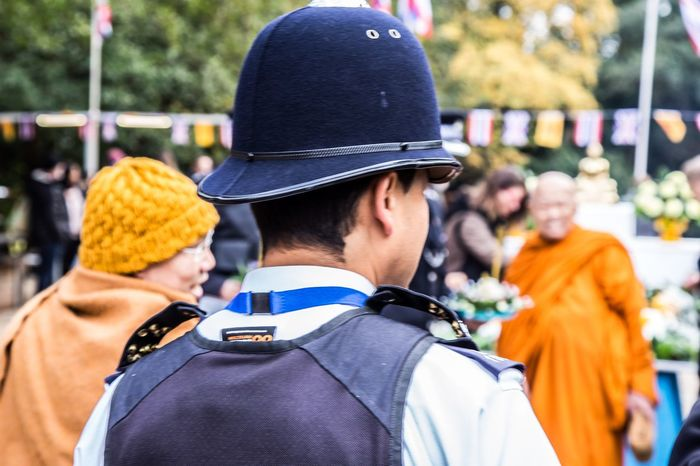 Policeman at a Thai temple in London during the Lai Krathong festival Thai Lai Krathong Budhaphadipa Temple London Thai Temple In London Clothing Hat Rear View Focus On Foreground Men Cap Group Of People Real People People Incidental People Police Force Adult Uniform Togetherness Outdoors Security Lifestyles Headshot Government