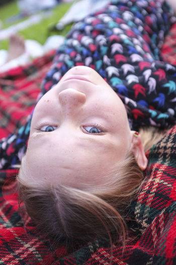Portrait Of Girl Lying On Picnic Blanket Outdoors