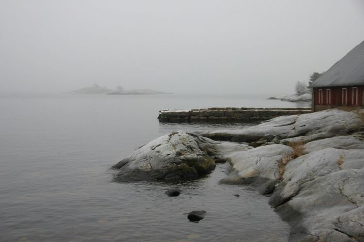 Rocks by seashore against foggy sky