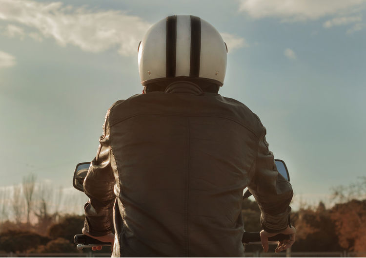 Rear view of man riding motorcycle against sky
