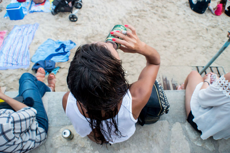 Woman Drinking Beer At The Beach