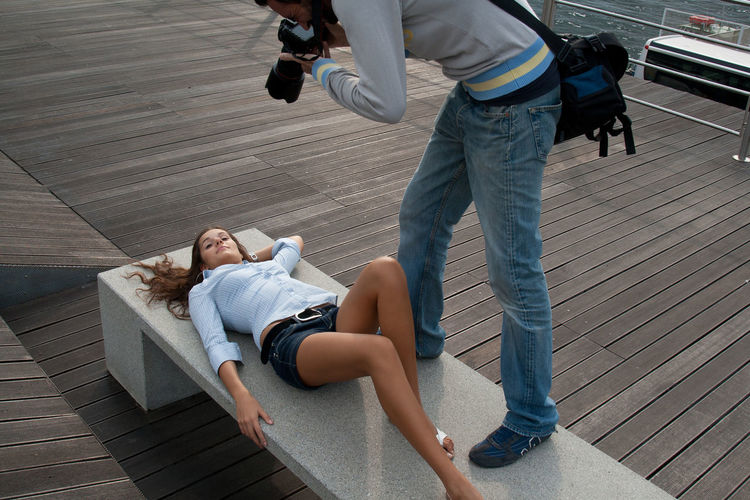 Photographer photographing young woman lying on bench at boat deck