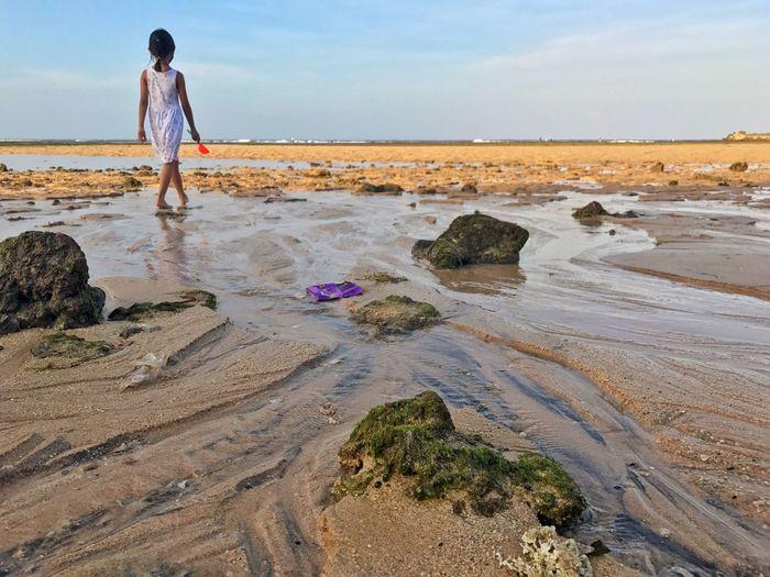 Girl walking at beach against sky