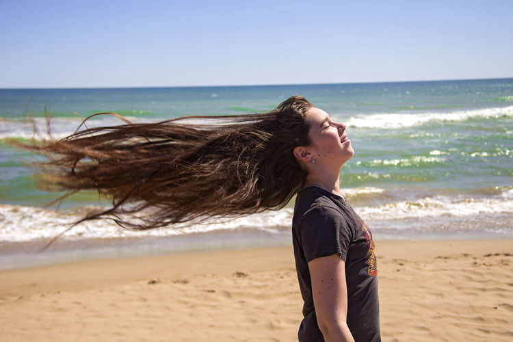Girl with long flowing hair on the sea shore Beach Beautiful Beauty In Nature Casual Clothing Coastline Disheveled Flowing Hair Girl The Portraitist - 2016 EyeEm Awards Horizon Over Water Let Your Hair Down Long Hair Girl Power Feel The Journey Portrait Sand Sea Seaside Shore Summer Sunny Day Vacations Waves Windy