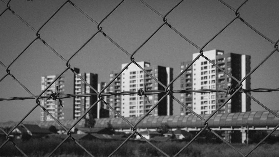 Full frame shot of chainlink fence against buildings in city