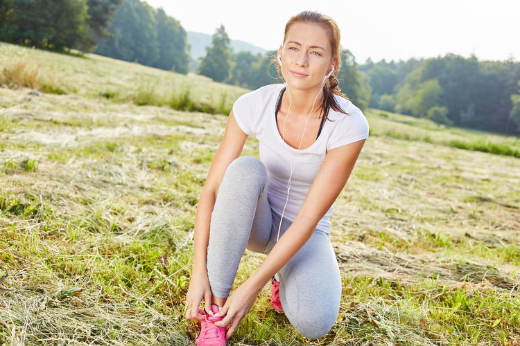 Young Woman Listening Music While Tying Shoelace On Field